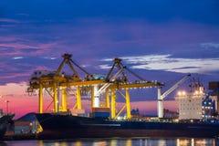Nave industrial de la carga del cargo del envase con el trabajo en el crepúsculo Foto de archivo libre de regalías
