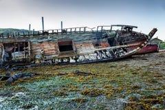 Nave oxidada abandonada vieja que se coloca en una playa arenosa Imagen de archivo