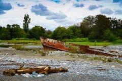 Nave oxidada trenzada varado en la playa con los guijarros en el Mar Negro imagenes de archivo