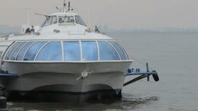 Nave passeggeri che oscilla nelle onde sulla banchina del fiume stock footage