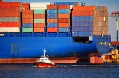 Nave porta-container blu gigante e piccolo rimorchiatore rosso Immagine Stock Libera da Diritti