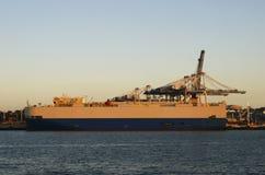 Nave rotolo-fuori/roll-on attraccata alle gru del contenitore e del pilastro al pilastro di porto di Auckland al tramonto, Nuova  immagine stock
