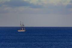 Nave solitaria de la vela en un horizonte azul, claro, océano tranquilo Fotografía de archivo