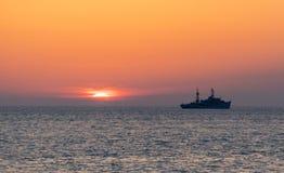 Nave y puesta del sol sobre el mar Imagen de archivo