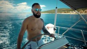 Navegación barbuda joven del hombre en el mar almacen de video