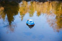 Navegación de la nave del juguete en el río en la puesta del sol foto de archivo
