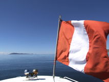 Navegación debajo de la bandera peruana en el lago Titicaca Imagen de archivo