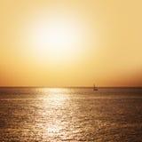 Navegación del barco en el mar en la puesta del sol Imagen de archivo libre de regalías