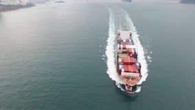 Navegación del buque de carga del envase en el agua tranquila del océano en un día nublado en la niebla en tiro de la antena 4k almacen de metraje de vídeo