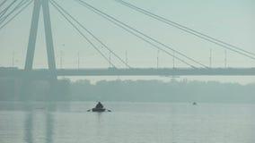 Navegación del pescador debajo del puente grande en el barco inflable, tiempo brumoso, ciudad grande metrajes