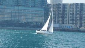 Navegación del velero en el mar cerca del lado de mar de la ciudad en un día soleado Imagen de archivo
