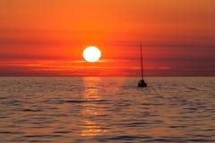 Navegación del yate contra puesta del sol Fotos de archivo libres de regalías