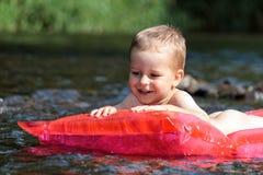 Navegación joven feliz del muchacho en el río Imágenes de archivo libres de regalías