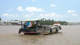 Navegación vietnamita tradicional del barco en el río Mekong delante de fábricas de proceso del coco, Vietnam metrajes