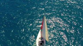 Navegaci?n del yate en el mar abierto en el d?a soleado Barco de navegación con una vela roja metrajes