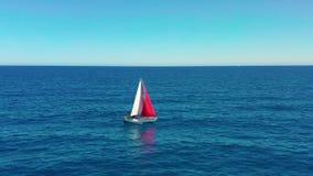 Navegaci?n del yate en el mar abierto en el d?a soleado Barco de navegación con una vela roja almacen de metraje de vídeo