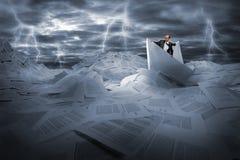 Navegación del hombre de negocios en el mar tempestuoso de los papeles Fotos de archivo libres de regalías