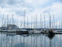 Navegando los yates se colocan con las velas bajadas en un pequeño puerto en un día nublado fotos de archivo