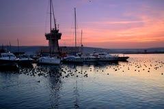 Navegue el puerto, la torre de control, las fochas y el cielo púrpura Fotos de archivo