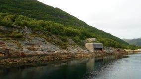 Navegue la navegación a lo largo de la costa montañosa verde con el fortín de la Segunda Guerra Mundial en aguas tranquilas en al metrajes