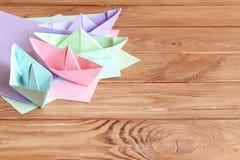 Naves coloridas plegamiento de papel, hojas del documento coloreado sobre una tabla de madera con el espacio vacío para el texto Fotos de archivo
