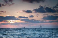 Naves en el mar en la puesta del sol Foto de archivo