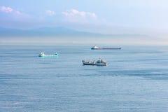 Naves en el puerto en un fondo de montañas y de nubes Imágenes de archivo libres de regalías