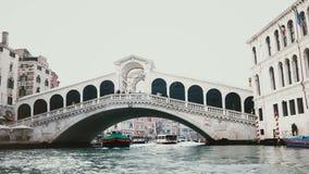 Naves que pasan bajo sorprender el puente de Rialto, uno de símbolos de Venecia, Italia y la herencia antigua de la arquitectura  almacen de video