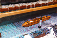 Navetta di tessitura sul filo di ordito blu in telaio Fotografia Stock