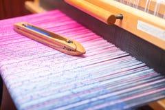 Navetta di tessitura sul filo di ordito di colore in telaio Fotografia Stock