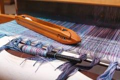 Navette de tissage sur la chaîne bleue dans la machine de tissage Photos stock