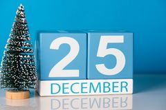 Navidad 25 de diciembre Día 25 del mes de diciembre, calendario con poco árbol de navidad en fondo azul Flor en la nieve Imagen de archivo libre de regalías