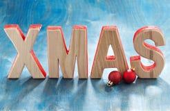 Navidad de madera decorativa de las letras en un fondo azul Imagenes de archivo