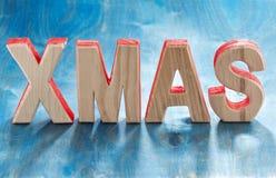 Navidad de madera decorativa de las letras en un fondo azul Fotografía de archivo