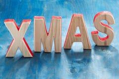Navidad de madera decorativa de las letras en un fondo azul, horizontal Foto de archivo