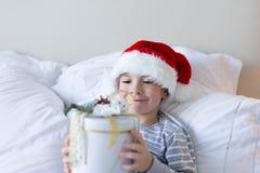 Navidad feliz y Año Nuevo El muchacho sonriente feliz en el sombrero rojo de Papá Noel se sienta en la cama que sostiene la actua foto de archivo libre de regalías
