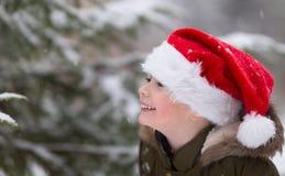 Navidad feliz y Año Nuevo Muchacho sonriente feliz en el sombrero rojo de Papá Noel Foto al aire libre del invierno Espacio libre fotos de archivo libres de regalías