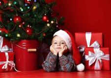 Navidad feliz y Año Nuevo Retrato del niño en regalos de la Navidad del sombrero rojo de Papá Noel que esperan para imágenes de archivo libres de regalías