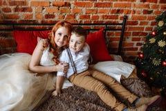Navidad Madre e hijo que se sientan en una cama en un cuarto con una pared de ladrillo Foto de archivo