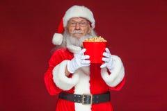 Navidad Santa Claus en los guantes blancos que sostienen un cubo rojo de palomitas con dos manos, movimientos él adelante y ofert imagenes de archivo