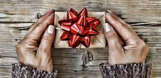 Navidad Una mujer sostiene un regalo de la Navidad adornado con el arco rojo Año Nuevo Día del `s de la tarjeta del día de San Va Fotos de archivo libres de regalías