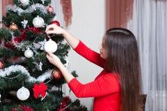 Navidad, vacaciones de invierno y concepto de la gente - mujer joven feliz que adorna el árbol de navidad con la bola en casa Fotos de archivo