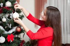 Navidad, vacaciones de invierno y concepto de la gente - mujer joven feliz que adorna el árbol de navidad con la bola en casa Fotos de archivo libres de regalías