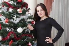 Navidad, vacaciones de invierno y concepto de la gente - mujer joven feliz que adorna el árbol de navidad con la bola en casa Imagenes de archivo
