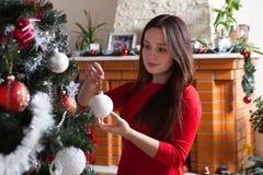 Navidad, vacaciones de invierno y concepto de la gente - mujer joven feliz que adorna el árbol de navidad con la bola en casa Foto de archivo