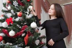 Navidad, vacaciones de invierno y concepto de la gente - mujer joven feliz que adorna el árbol de navidad con la bola en casa Fotografía de archivo