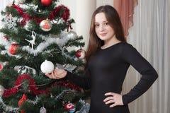 Navidad, vacaciones de invierno y concepto de la gente - mujer joven feliz que adorna el árbol de navidad con la bola en casa Imagen de archivo libre de regalías