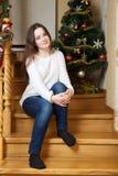 Navidad, vacaciones de invierno y concepto de la gente - mujer joven feliz que adorna el árbol de navidad con la bola en casa Imágenes de archivo libres de regalías