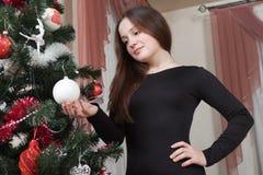 Navidad, vacaciones de invierno y concepto de la gente - mujer joven feliz que adorna el árbol de navidad con la bola en casa Fotografía de archivo libre de regalías