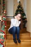 Navidad, vacaciones de invierno y concepto de la gente - mujer joven feliz que adorna el árbol de navidad con la bola en casa Foto de archivo libre de regalías